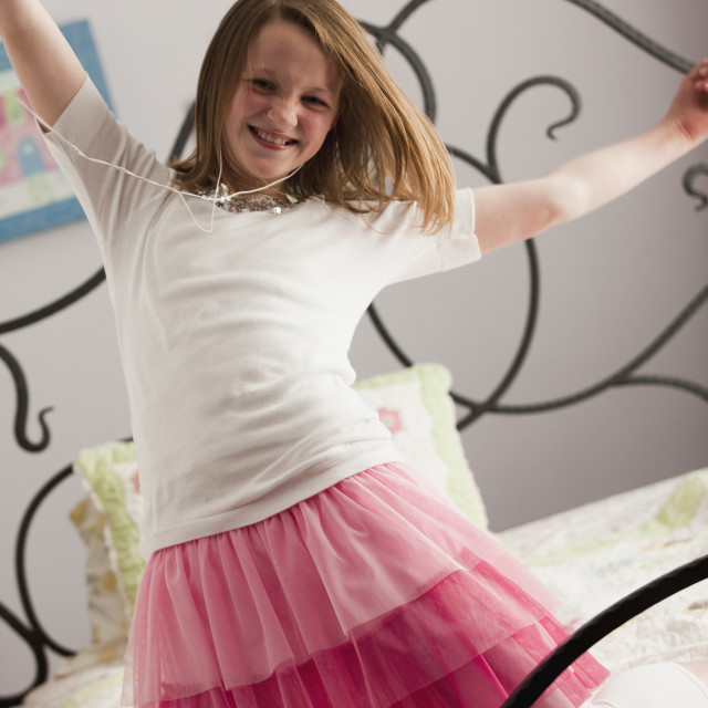 """""""Young girl dancing on her bed"""" stock image"""