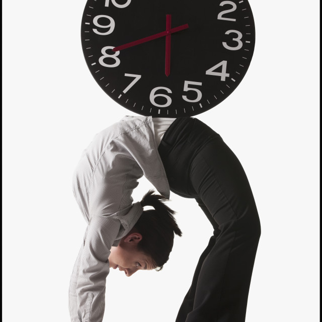 """Clock on top of businesswoman bending over backwards"" stock image"