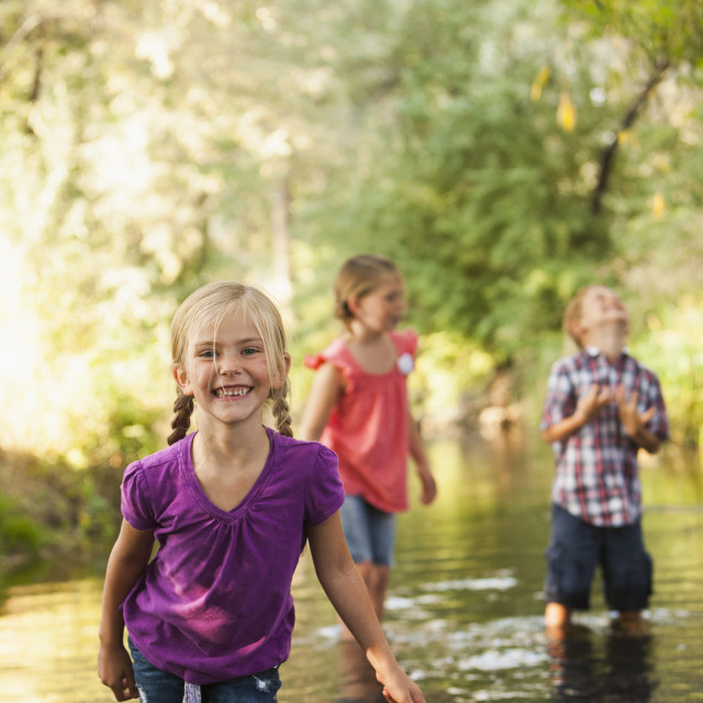 """Little girl (4-5) in foreground standing in small stream with friends (6-7)"" stock image"