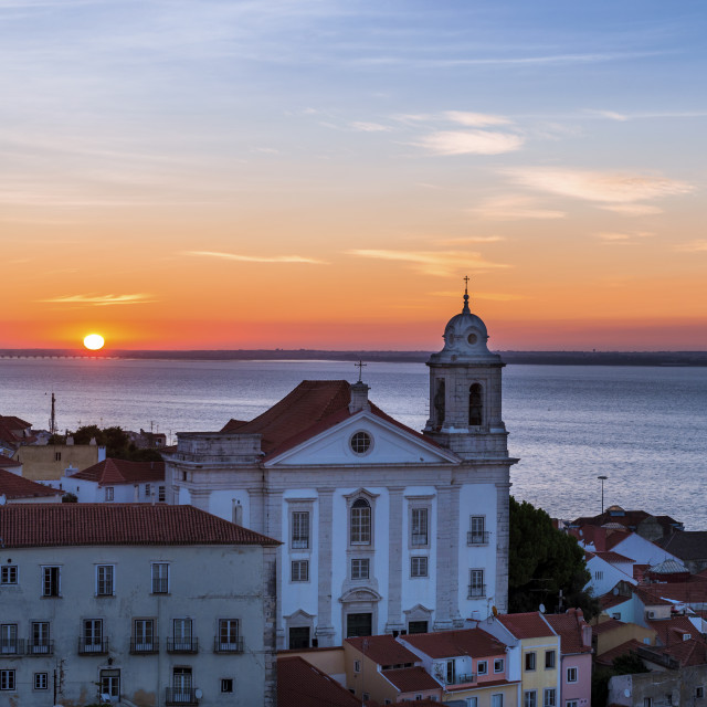 """View of a Church in the Alfama neighborhood from the Portas do Sol viewpoint at sunrise in Lisbon, Portugal; Concept for travel in Portugal, visit Portugal and most beutiful places in Portugal"" stock image"