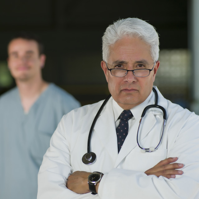 """""""Portrait of senior doctor with orderly in background"""" stock image"""