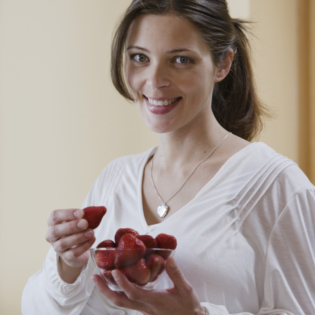 """Portrait of expecting mother eating strawberries"" stock image"