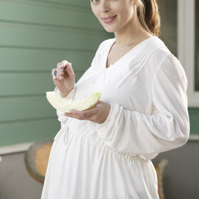 """Portrait of expecting mother eating melon"" stock image"