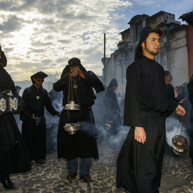 """Antigua, Guatemala - April 19, 2014: Man wearing black robes and hoods spreading incense in a street of the city of Antigua during a procession of the Holy Week in Antigua, Guatemala"" stock image"