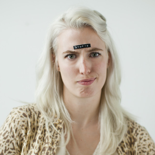 """""""Portrait of young woman with word stupid on forehead"""" stock image"""