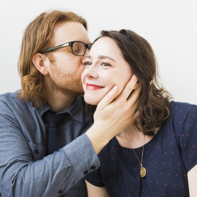"""Man kissing smiling young woman"" stock image"