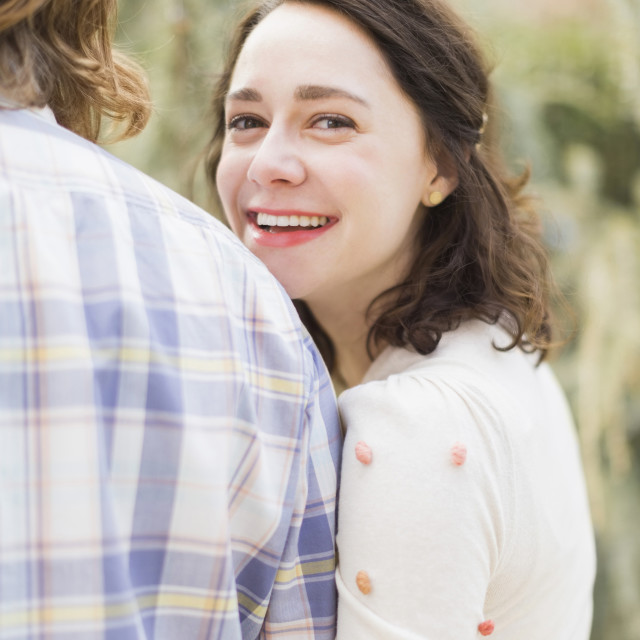 """Young smiling woman next to boyfriend"" stock image"