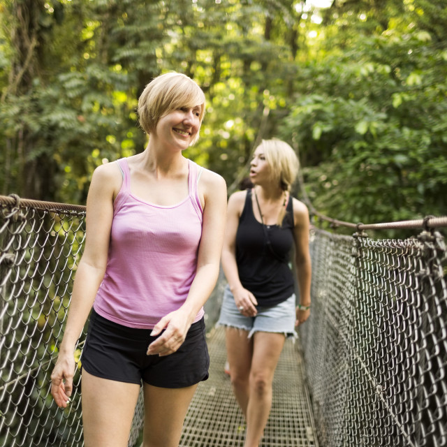 """""""Young women walking on footbridge in forest"""" stock image"""
