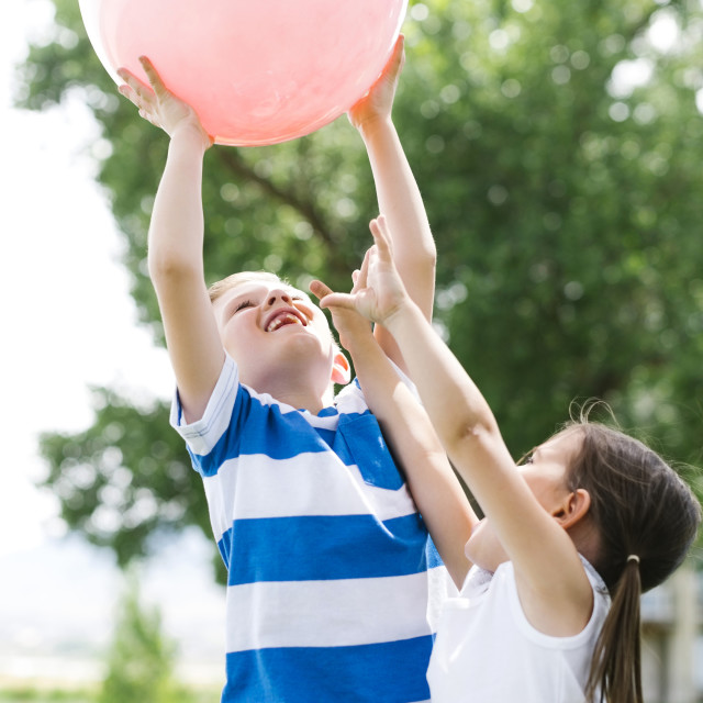 """""""Boy (6-7) and girl (4-5) holding pink ball"""" stock image"""