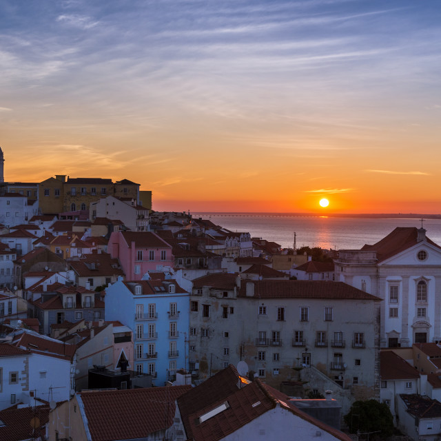 """View of the Alfama neighborhood from the Portas do Sol viewpoint at sunrise in Lisbon, Portugal; Concept for travel in Portugal, visit Portugal and most beutiful places in Portugal"" stock image"