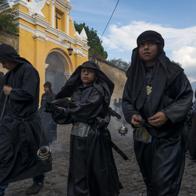 """Antigua, Guatemala - April 19, 2014: Young boys wearing black robes and hoods spreading incense in a street of the city of Antigua during a procession of the Holy Week in Antigua, Guatemala"" stock image"