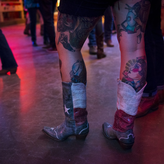 """Austin, Texas - June 13, 2014: Detail of the boots and tattoed legs of a young woman in the Broken Spoke dance hall in Austin, Texas, USA"" stock image"