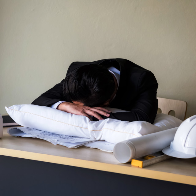 """""""Tired businessman sleep on pillow at office table"""" stock image"""