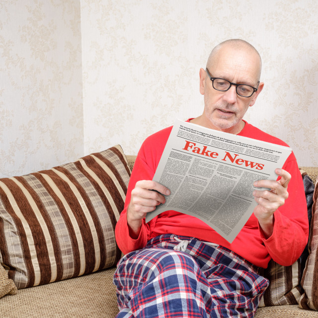 """Man reading fake news on a daily paper"" stock image"
