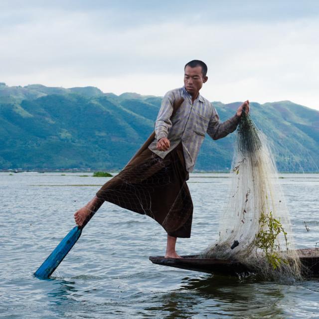 """""""NYAUNGSHWE, MYANMAR - 9 JUN 2014: Leg-paddling while fishing is a traditional..."""" stock image"""