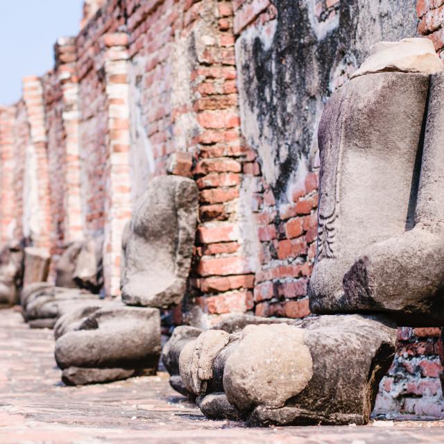 """Series of sitting stone Buddha sculptures along a brick wall in Wat Maha Tat,..."" stock image"