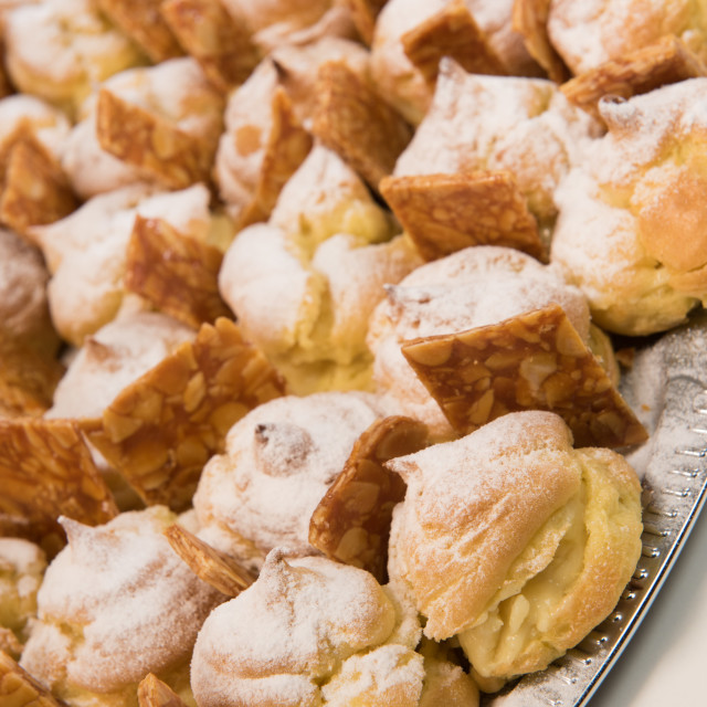 """""""Cream puffs filled vanilla custard and dusted with icing on a plat and nougatine"""" stock image"""