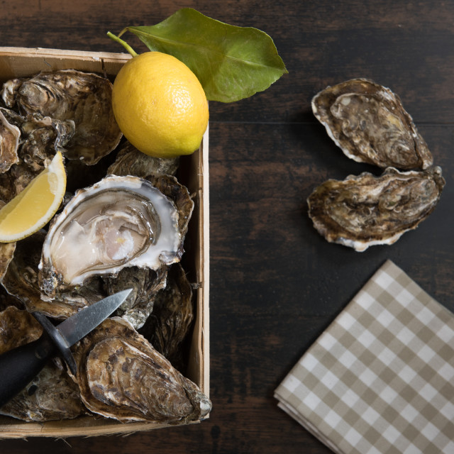 """""""Raw oysters basket with lemon on wood board and bottle of wine and glass"""" stock image"""