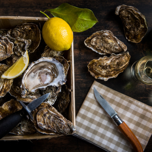 """Raw oysters basket with lemon on wood board and bottle of wine and glass"" stock image"