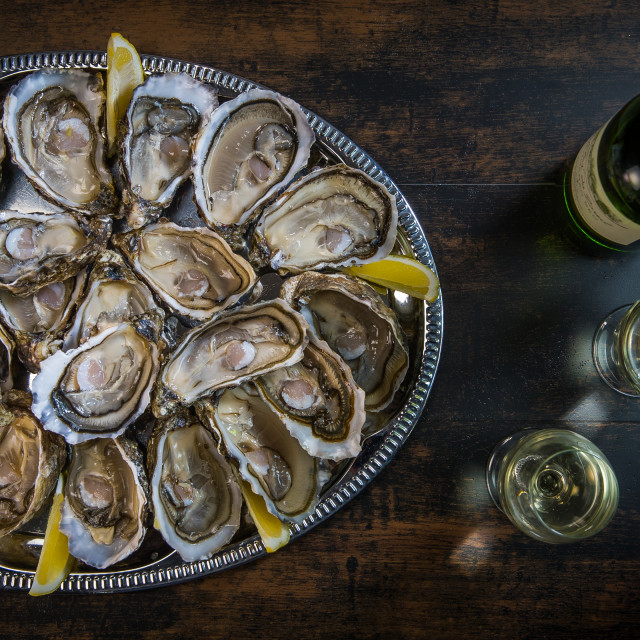 """fresh oysters dishing up with lemon on the table"" stock image"