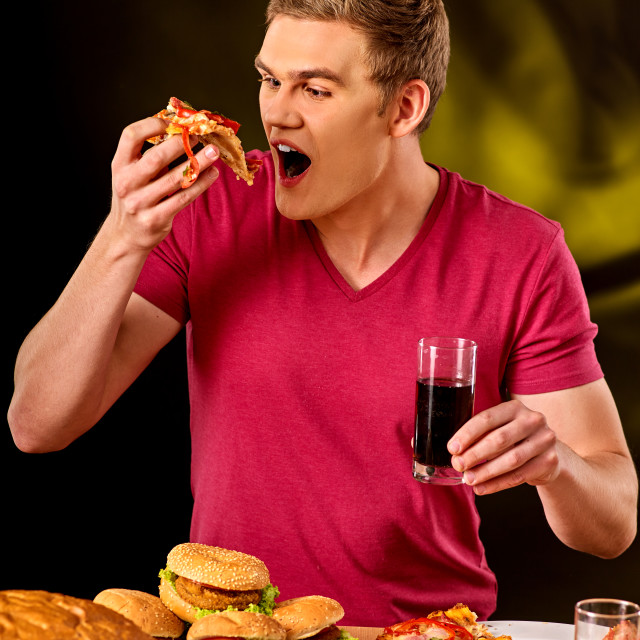 """""""Young man eating slice of pizza ."""" stock image"""