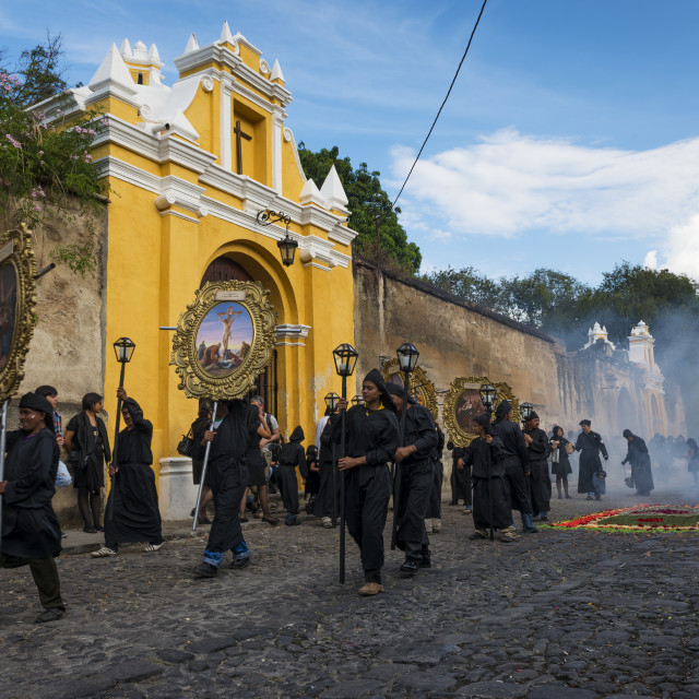 """Antigua, Guatemala - April 19, 2014: People wearing black robes and hoods during a procession of the Holy Week in Antigua, Guatemala"" stock image"