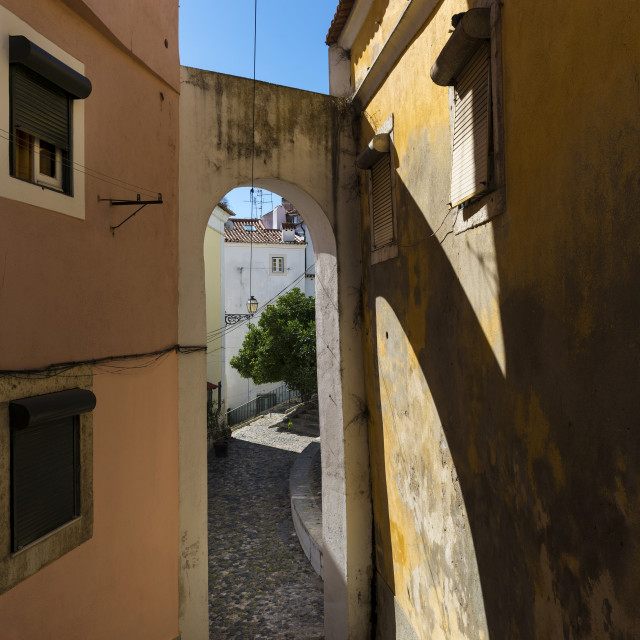 """View of a narrow street with an arch and traditional old buildings in the historic neighborhood of Alfama in Lisbon, Portugal; Concept for visit Lisbon"" stock image"