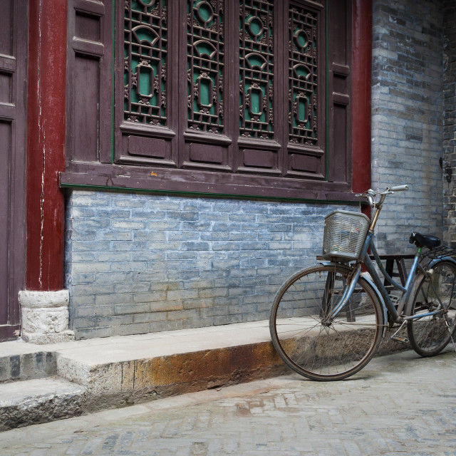 """A bicycle parked against an ornamented wall in the Great Mosque in the city of Xian, China, Asia"" stock image"
