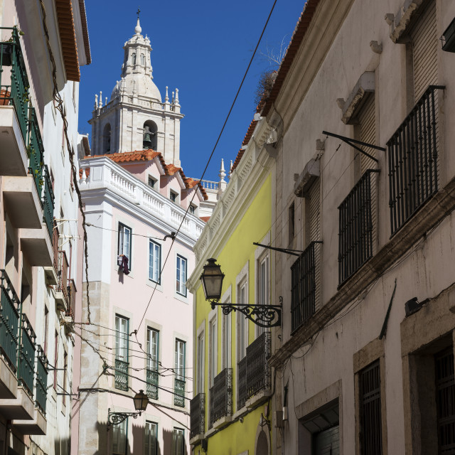 """View of a narrow street and buildings with a tower of the Sao Vincente de Fora church on the backrgound, in the historic neighborhood of Alfama in Lisbon, Portugal; Concept for visit Lisbon"" stock image"