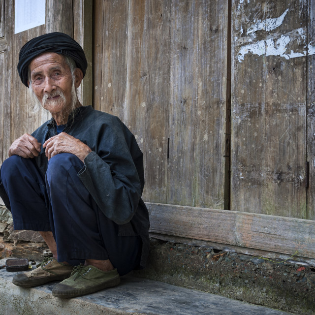 """Dazhai, China - August 4 ,2012: An old chinese man sitting on the door of an old building in the village of Dazhai in China, Asia"" stock image"
