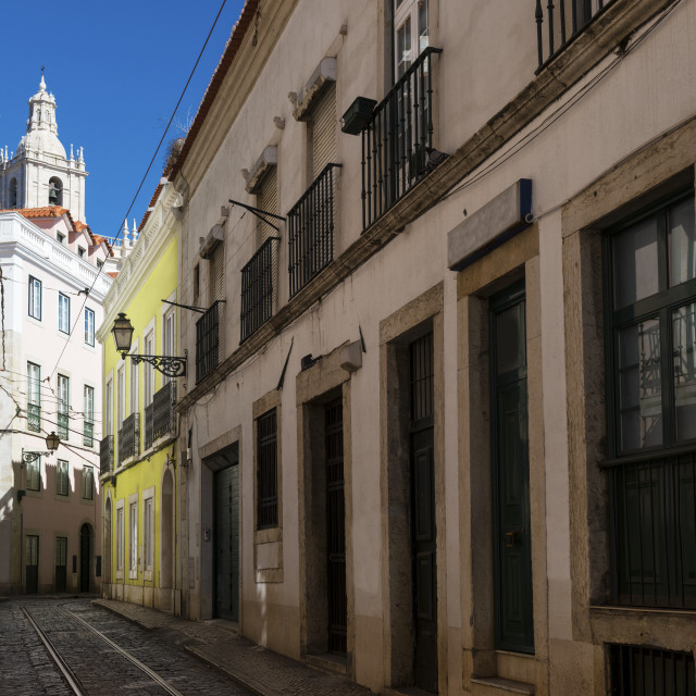 """""""View of a narrow street and buildings with a tower of the Sao Vincente de Fora church on the backrgound, in the historic neighborhood of Alfama in Lisbon, Portugal; Concept for visit Lisbon"""" stock image"""
