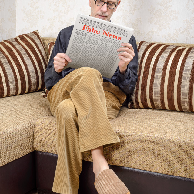 """""""Man reading fake news on a daily paper"""" stock image"""