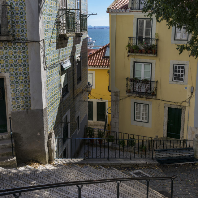 """""""Beautiful and colorful old buildings in the Alfama Neighborhood and the Tagus River on the background on a sunny day; Concept for travel in Portugal and visit Lisbon"""" stock image"""