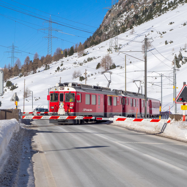 """Level crossing of Bernina red train"" stock image"