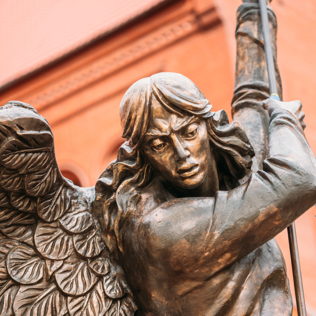 """""""Statue Of Archangel Michael With Outstretched Wings Before Red Catholic Church"""" stock image"""
