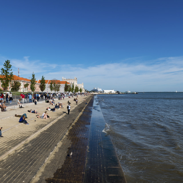 """""""Lisbon, Portugal - October 22, 2017: Tourists enjoying a sunny day in the banks of the Tagus River along Ribeira das Naus Avenue in the city of Lisbon, Portugal"""" stock image"""