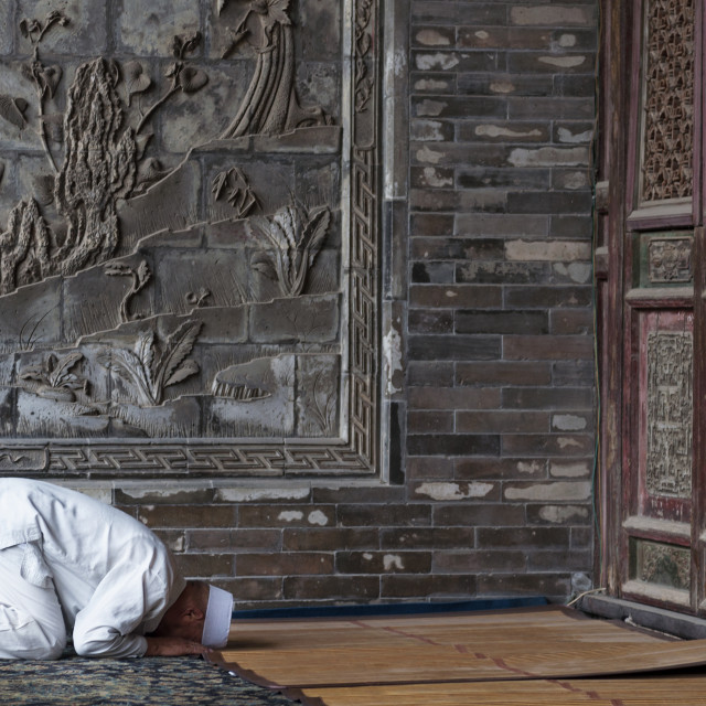 """Xi'An, China - August 5, 2012, 2017: One man praying at the Xi'An Great Mosque in the city of Xi'An in China, Asia."" stock image"