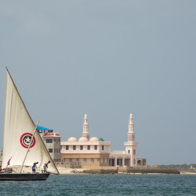 """Dhow sailing in front of the new Lamu mosque, Lamu, Lamu Archipelago, Kenya"" stock image"