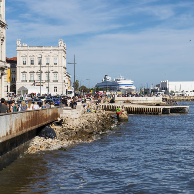 """""""Lisbon, Portugal - October 22, 2017: Tourists walking and enjoying a sunny day in the banks of the Tagus River along Ribeira das Naus Avenue in the city of Lisbon with the Cais do Sodré in the background, Portugal"""" stock image"""