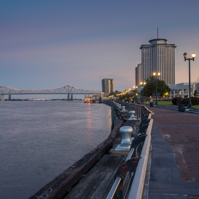 """""""New Orleans, Louisiana - June 17, 2014: View of the Mississippi river from the city of New Orleans riverfront, with the Great New Orleans Bridge on the background in New Orleans, Louisiana, at dusk."""" stock image"""