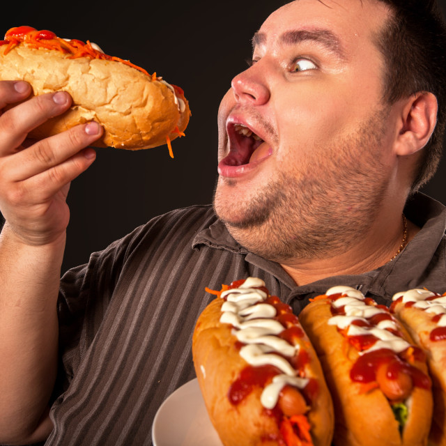 """""""Fat man eating fast food hot dog. Breakfast for overweight person."""" stock image"""