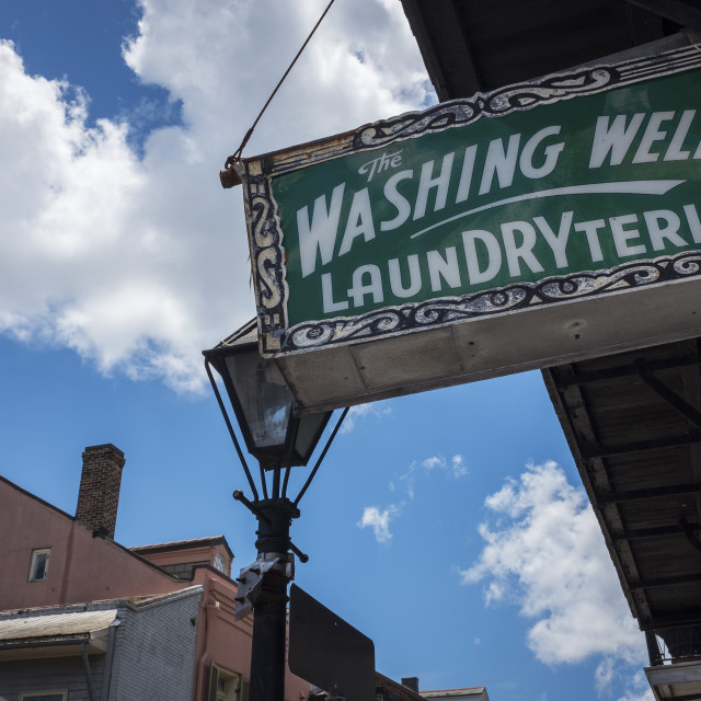 """""""New Orleans, Louisiana - June 18, 2014: An old and rusty billboard for a laundry store in the French Quarter in New Orleans, Louisiana, USA."""" stock image"""