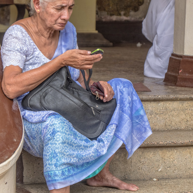 """Old woman sits in front of the Buddhist temple"" stock image"