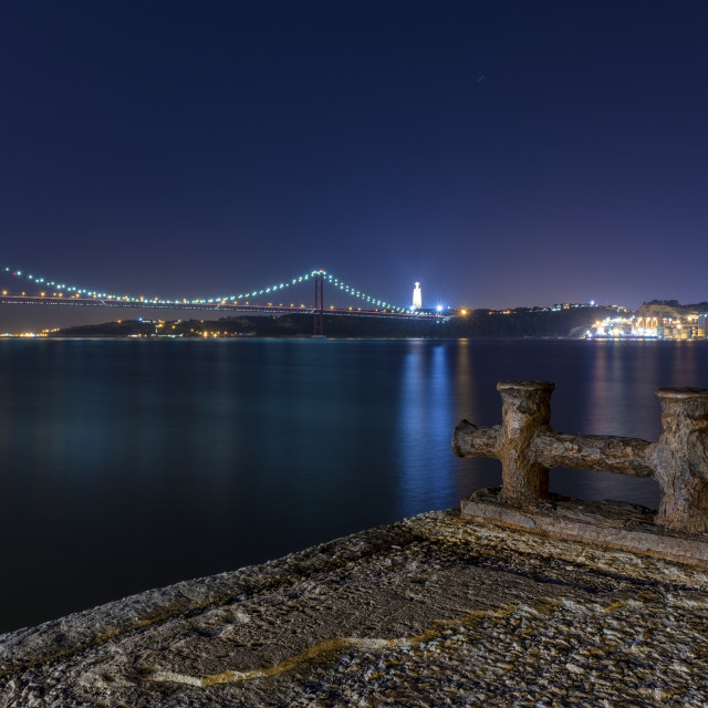 """""""Detail of an old pier in the banks of the Tagus River (Rio Tejo) with the 25 of April Bridge on the backgound at night; Concept for visit Lisbon and most beaufiful places in Portugal"""" stock image"""