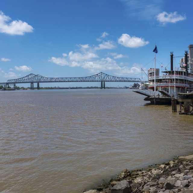 """New Orleans, Louisiana - June 17, 2014: View of the Mississippi river from the city of New Orleans riverfront, with a Mississippi Steamboat and the Great New Orleans Bridge on the background in New Orleans, Louisiana."" stock image"