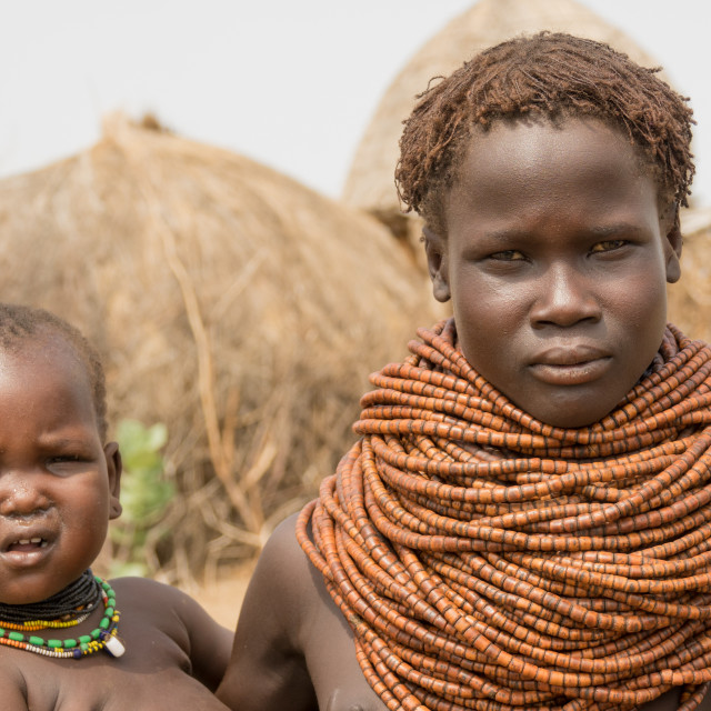 """Young Nyangatom woman with her baby, Kangate, Omo Valley, Ethiopia"" stock image"
