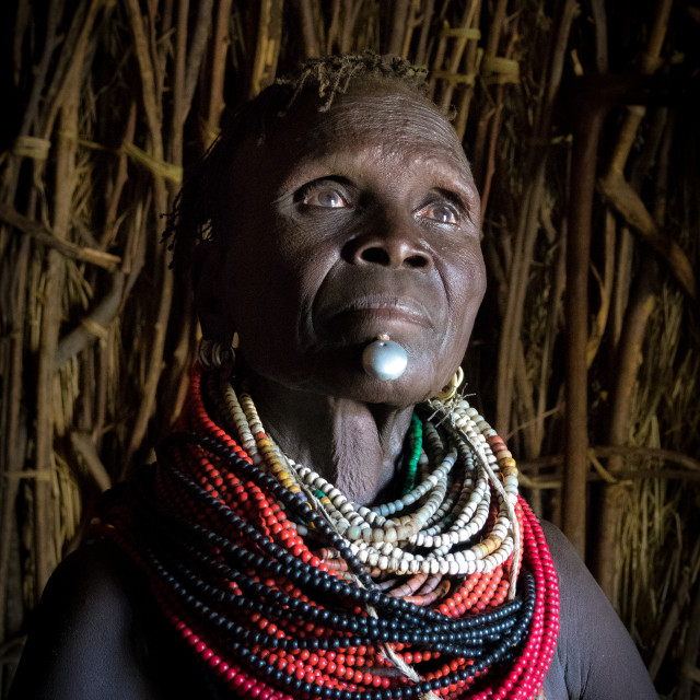 """Old Nyangatom woman in her hut, Kangate, Omo Valley, Ethiopia"" stock image"