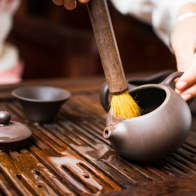 """Female brushing tea kettle during during traditional Chinese tea"" stock image"