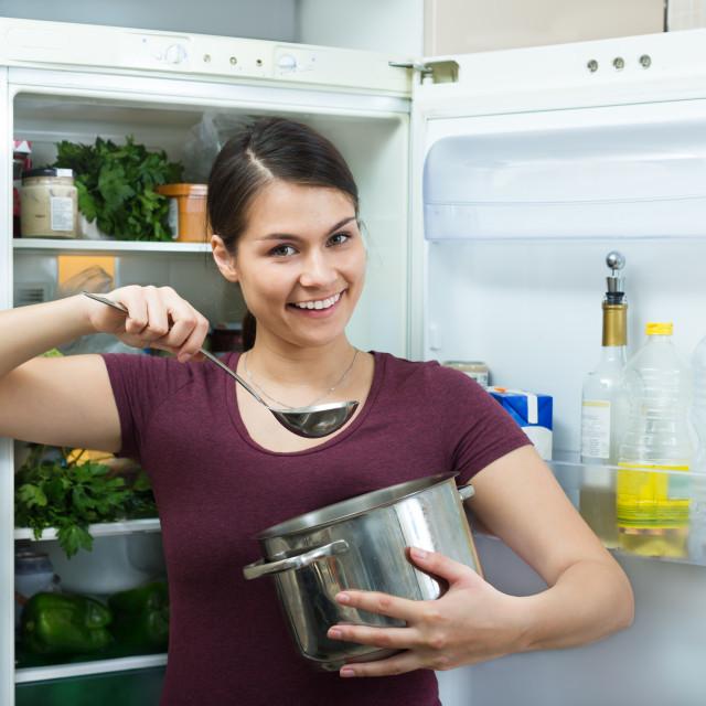"""""""Hungry brunette standing near fridge"""" stock image"""
