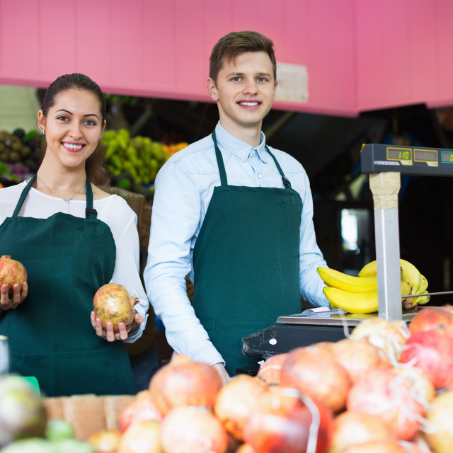 """""""Smiling positive sellers having vegetables and fruits on displays"""" stock image"""